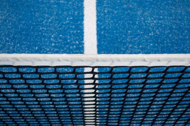 Blauwe netto peddeltennis en de achtergrond van het hofgebied Premium Foto