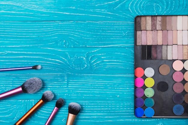 Blauwe oppervlak met poeders en make-up kwasten Gratis Foto