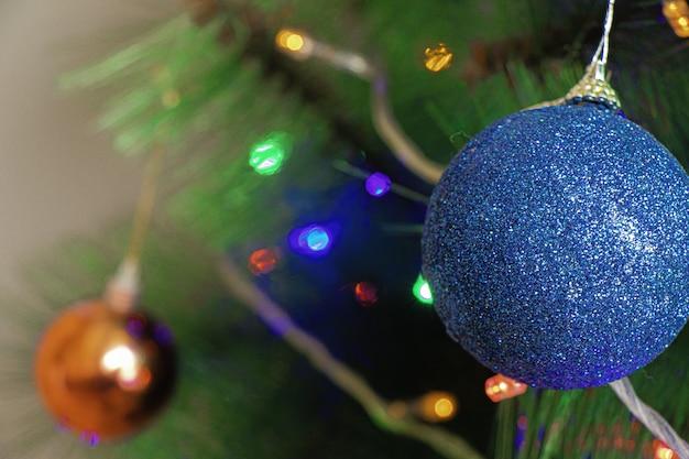 Blauwe ornamentdecoratie op de kerstboom onder de lichten Gratis Foto