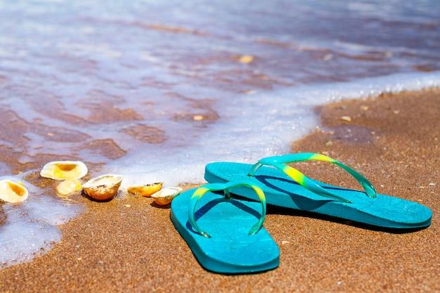 Blauwe pantoffels staan op het zand aan de kust Premium Foto