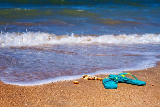 Blauwe pantoffels staan op het zand aan de kust. Premium Foto