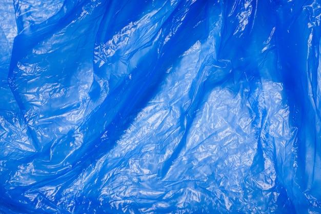 Blauwe plastic zak die de natuur, textuur schaadt Premium Foto
