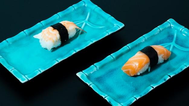 Blauwe platen met sushi op een zwarte achtergrond Gratis Foto