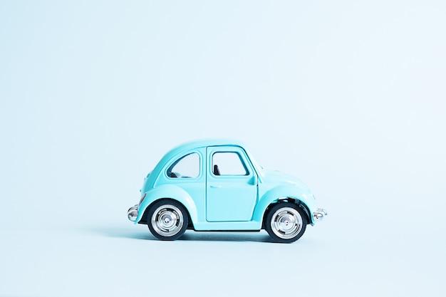 Blauwe retro speelgoedauto op blauw Premium Foto