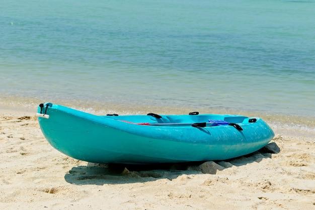 Blauwe roeiboot op het strand met de prachtige oceaan op de achtergrond Gratis Foto