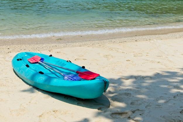 Blauwe roeiboot op het strand met de prachtige oceaan Gratis Foto