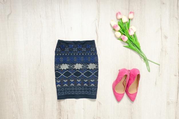 Blauwe rok met ornament, roze schoentjes en boeket tulpen. modieus concept Premium Foto