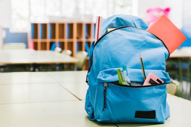 Blauwe schoolkindrugzak op lijst Gratis Foto