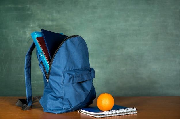 Blauwe schooltas met schrift en oranje Gratis Foto