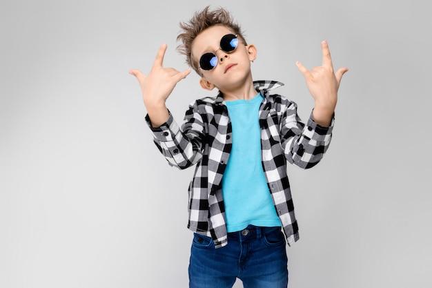 Blauwe shirt en spijkerbroek staat op een grijze achtergrond. de jongen draagt een ronde bril. roodharige jongen toont een rocker geit Premium Foto