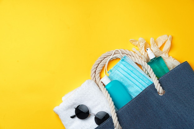 Blauwe strandtas met strandaccessoires en beschermend masker op gele achtergrond Premium Foto