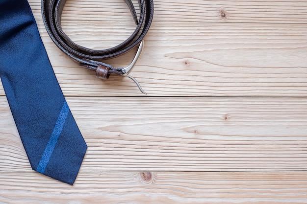 Blauwe stropdas met riem op houten achtergrond met exemplaarruimte voor tekst. Premium Foto