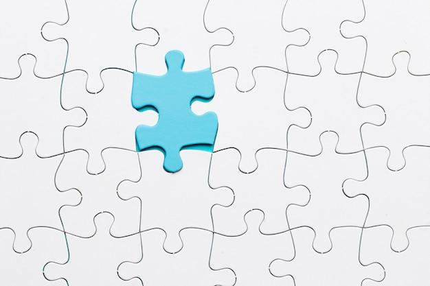 Blauwe stuk puzzel verbonden met witte stuk achtergrond Gratis Foto