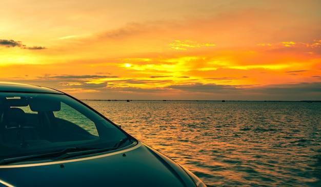 Blauwe suv-auto met sport en modern die ontwerp op betonweg door het overzees bij zonsondergang wordt geparkeerd. Premium Foto