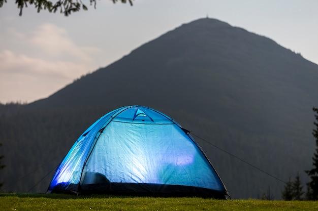 Blauwe tent op bosopheldering op verre bergachtergrond. Premium Foto