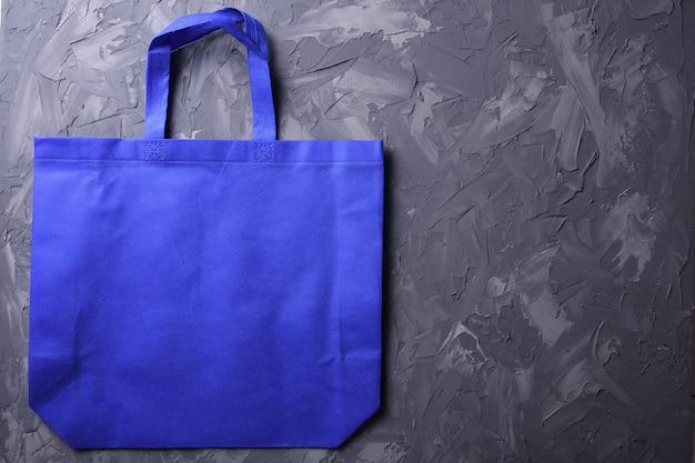 Blauwe textielzak op betonachtergrond Premium Foto