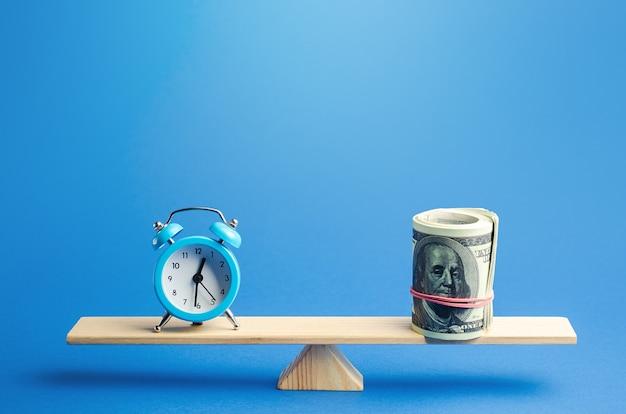 Blauwe wekker en een bundel dollars op schalen. redelijk uurloon. tijdregistratie Premium Foto