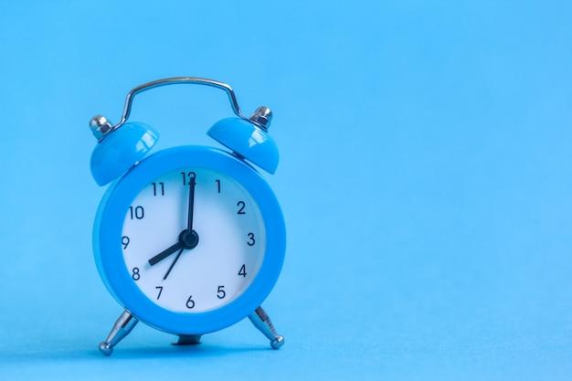 Blauwe wekker op blauw Premium Foto