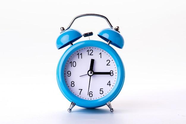 Blauwe wekker op een witte achtergrond Gratis Foto