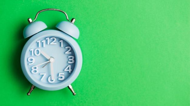 Blauwe wekker tegen groene achtergrond Gratis Foto