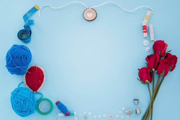 Blauwe wol; meetlint; draadspoel; knop; vingerhoedje en rozen op blauwe achtergrond Gratis Foto