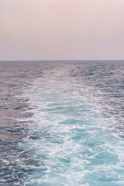 Blauwe zeewater spatten met reflecties van de zon. Gratis Foto