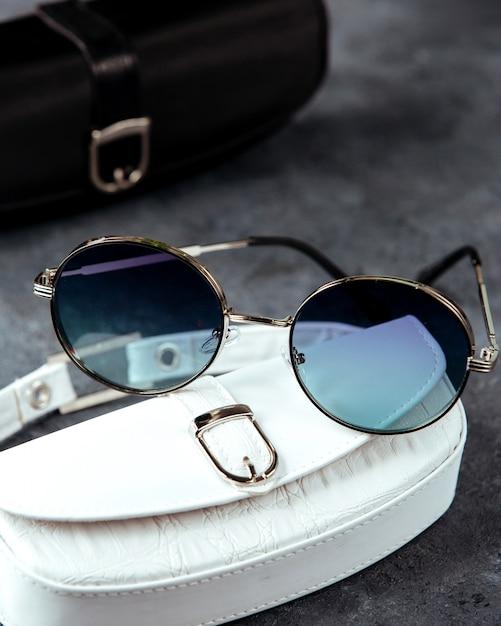 Blauwe zonnebril op de witte kast en grijze oppervlak Gratis Foto