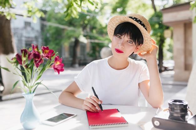 Blauwogige vrouwelijke student in strooien hoed huiswerk op terras, zittend met pen en notitieblok Gratis Foto
