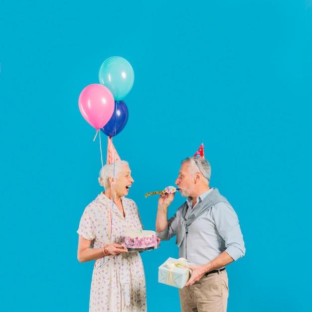 Blazende partijhoorn van de mens terwijl zijn verjaardagscake van de vrouwenholding op blauwe achtergrond Gratis Foto