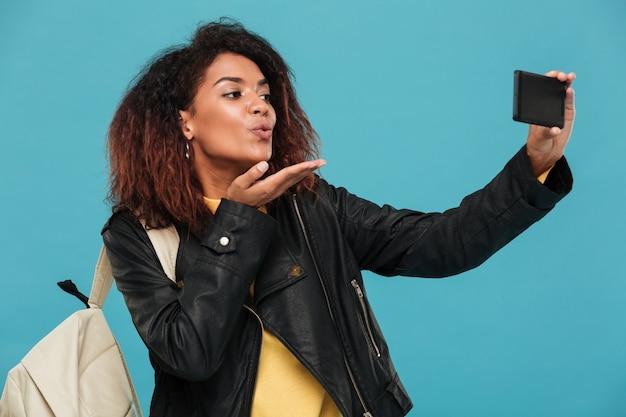 Blij afrikaanse vrouw in leren jas met rugzak selfie maken Gratis Foto