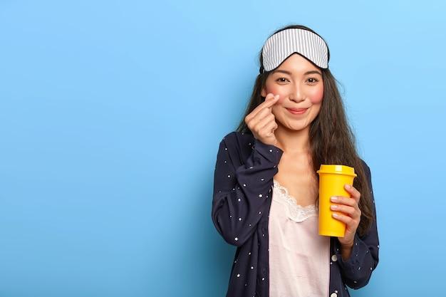 Blij asain donkerharige vrouw maakt koreaans als gebaar, gekleed in pyjama's en slaapmasker, houdt gele meeneem koffiekopje vast Gratis Foto