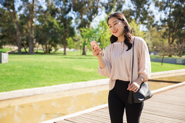 Blij aziatisch meisje dat grappige video's op telefoon bekijkt Gratis Foto