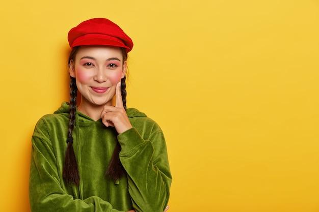 Blij aziatisch meisje houdt wijsvinger op de wang, kijkt vrolijk naar de camera, heeft rode wangen, draagt een rode baret en een groen fluwelen sweatshirt Gratis Foto
