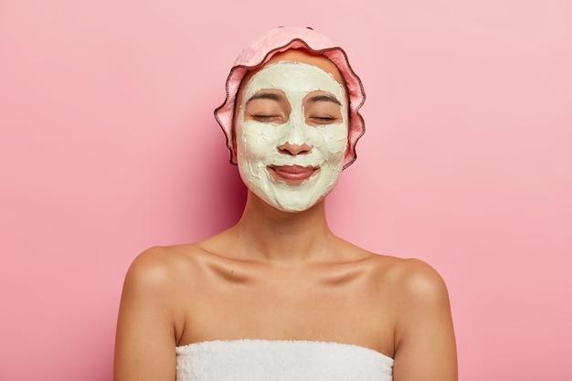 Blij aziatische vrouw draagt klei zuiverende organische masker op gezicht, heeft schoonheidsprocedures in spa salon, draagt roze zachte beschermende douchemuts Gratis Foto