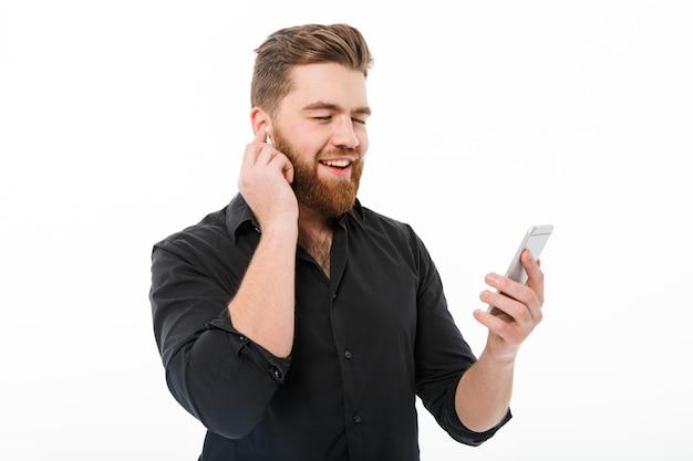 Blij bebaarde man in shirt luisteren muziek door smartphone Gratis Foto
