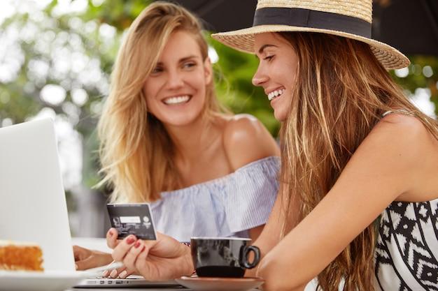 Blij brunette jonge vrouw in staw hat graag salaris ontvangen, geld uitgeven aan online winkelen, vrije tijd doorbrengen met vriend in café, genieten van koffie. mensen, e-commerce en betalingsconcept Gratis Foto