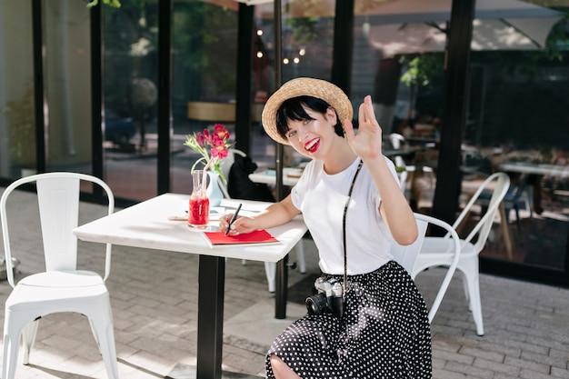 Blij dat brunette meisje schrijft in notitieblok en zwaaiende hand met glimlach, rusten in café Gratis Foto