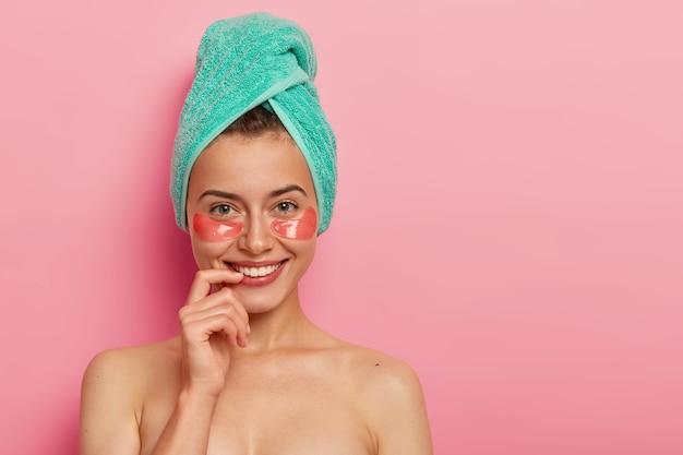 Blij dat de europese vrouw zorgt voor de tere huid rond de ogen, collageenpleisters aanbrengt, minimale make-up draagt, een badhanddoek om het hoofd wikkelt, naakt tegen een roze achtergrond staat. Gratis Foto
