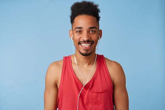 Blij dat jonge afro-amerikaanse knappe man zich geweldig voelt, draagt een rood shirt, luistert naar een nieuwe opwindende podcast, glimlacht breed Gratis Foto