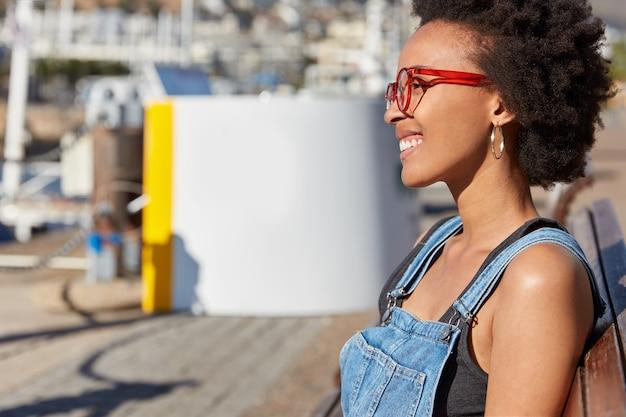 Blij dat jonge amerikaanse meid met knapperig haar, donkere huid, bril en vrijetijdskleding draagt, op een bank zit, geniet van vrije tijd, droomt van iets aangenaams. vrouwelijkheid, streetstyle en vrijetijdsconcept Gratis Foto