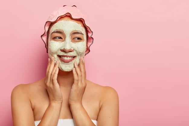 Blij dat jonge vrouw met klei gezichtsmasker, spa-procedures krijgt in de schoonheidssalon, verwent gezicht, staat verpakt in een zachte handdoek, geniet van zelfzorg, draagt waterdichte hoed Gratis Foto