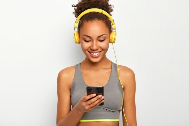 Blij dat sportieve krullende afro-amerikaanse vrouw luistert naar muziek in de koptelefoon, breed lacht, sportbeha draagt. Gratis Foto