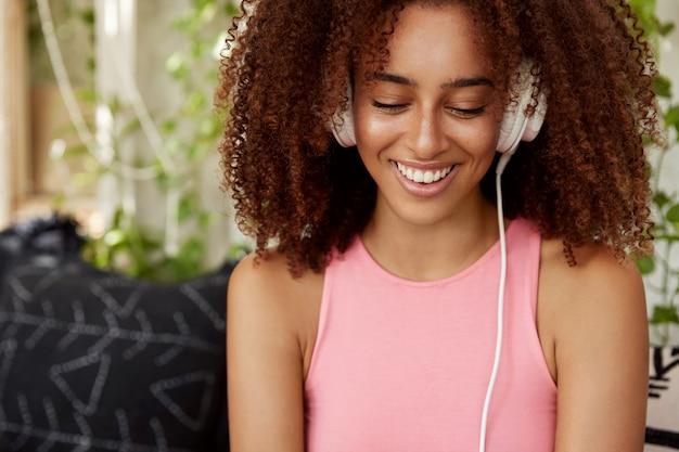 Blij dat vrouwelijke student met donkere huid, luisterboek in hoofdtelefoons luistert, verbonden met onherkenbaar apparaat. mooie jonge vrouw ontspannen coole muziek, zit tegen cafetaria interieur, geniet van vrije tijd Gratis Foto