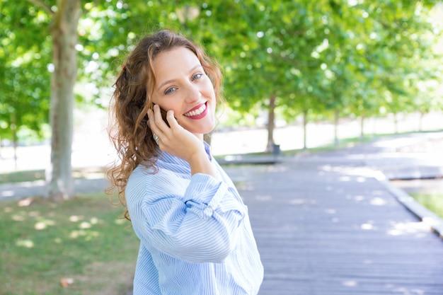 Blij gelukkig meisje dat op mobiele telefoon spreekt Gratis Foto
