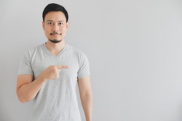 Blij gezicht van de mens in grijs t-shirt met hand punt op lege ruimte. Premium Foto