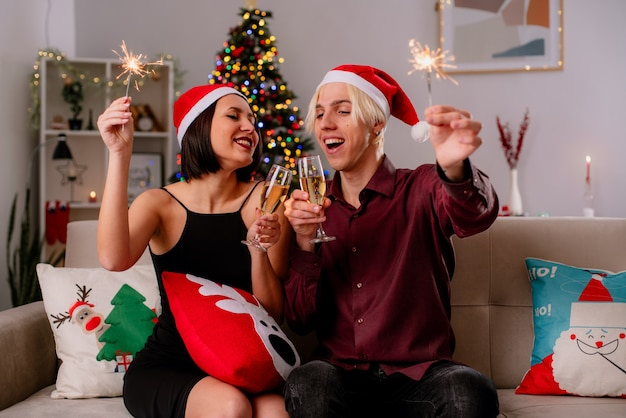 Blij jong koppel thuis in de kersttijd met kerstmuts zittend op de bank in de woonkamer Gratis Foto