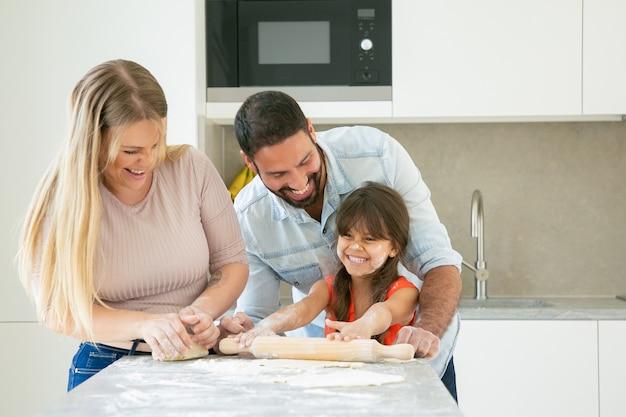 Blij jong stel en meisje met bloempoeder op gezicht lachen tijdens het samen bakken. Gratis Foto