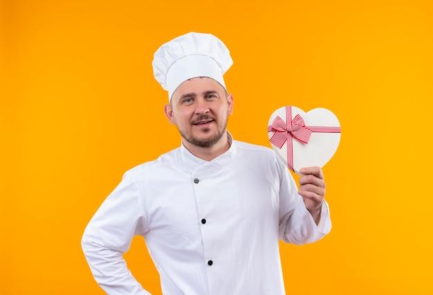 Blij jonge knappe kok in chef-kok uniform hartvormige geschenkdoos houden en vinger op geïsoleerde oranje ruimte Gratis Foto