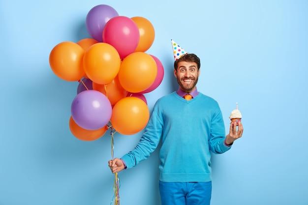 Blij jonge man met haren, houdt heerlijke kleine muffin, bos van gekleurde ballonnen Gratis Foto