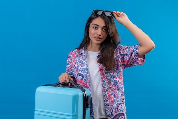 Blij jonge mooie reiziger vrouw met koffer aanraken van haar zonnebril op het hoofd glimlachend vriendelijk staande over blauwe achtergrond Gratis Foto